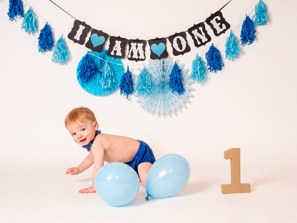 baby boy crawling with balloons celebrating first birthday