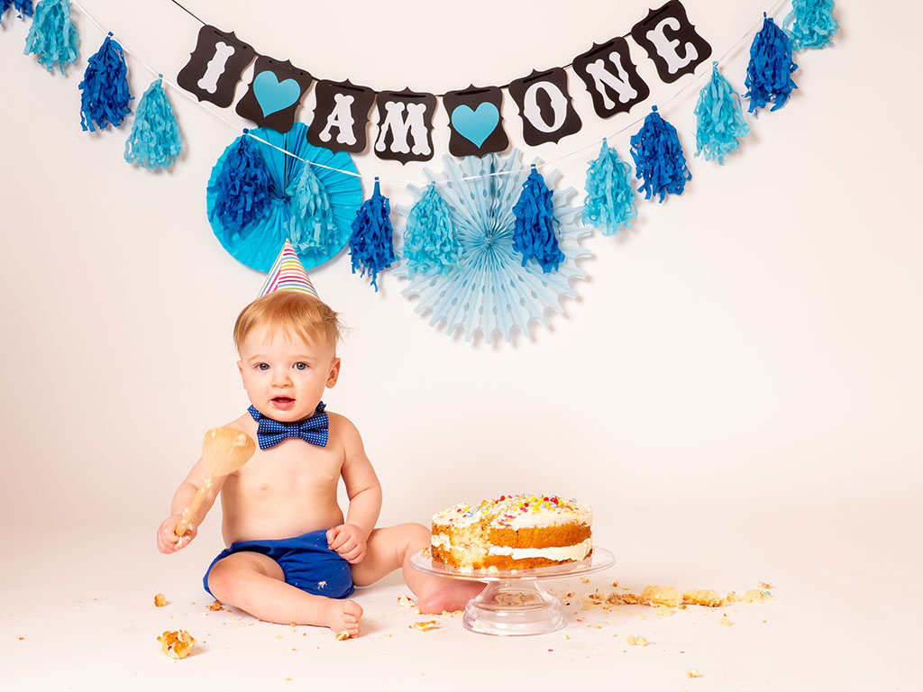 baby boy with birthday cake and wooden spoon