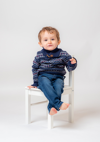 Toddler in knitted jumper sitting on white wooden chair with arm resting on back of chair