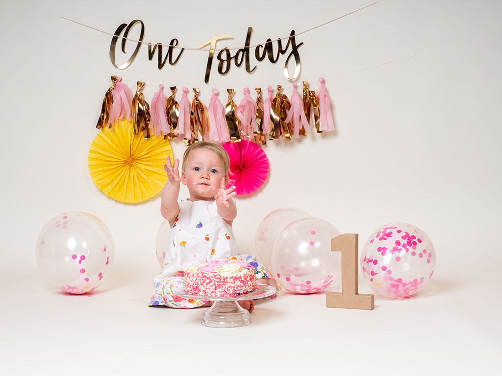 cake smash photography of little girl with birthday cake taken by qualified family photographer in Braintree, Essex