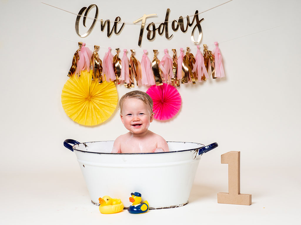 cake smash photography of little girl playing in bubble bath taken by qualified family photographer in Braintree, Essex