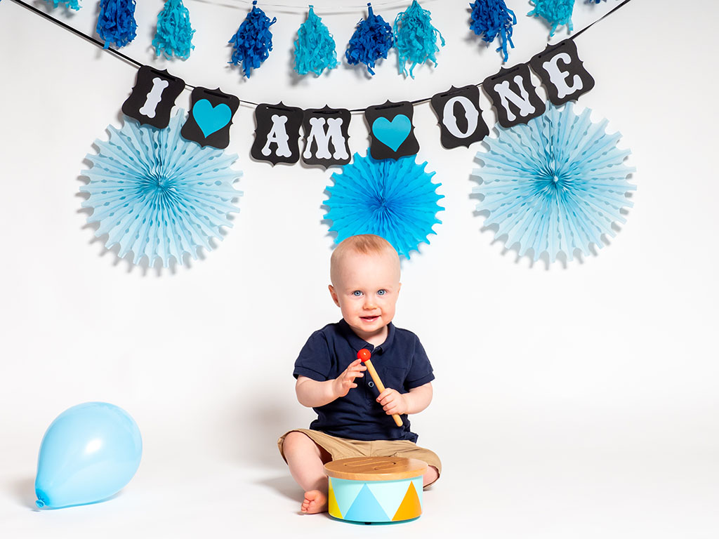 cake smash photography of little boy playing with drum taken by qualified family photographer in Braintree, Essex
