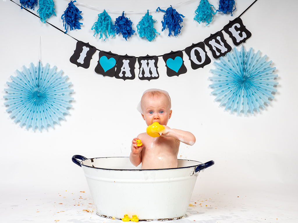 cake smash photography of little boy after cake smash in bubble bath taken by qualified family photographer in Braintree, Essex