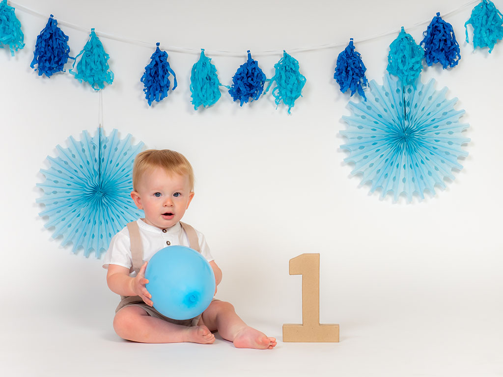 cake smash photography of little boy playing with balloon taken by qualified family photographer in Braintree, Essex