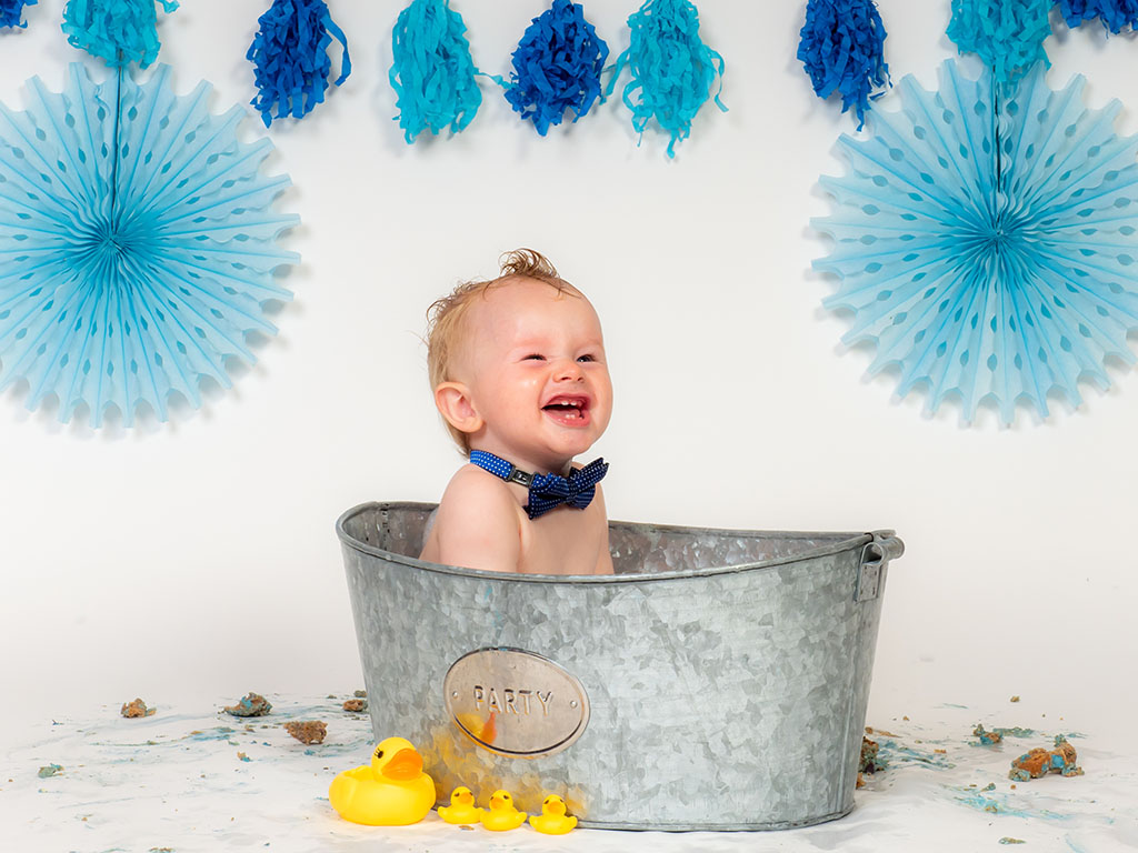 cake smash photography of little boy in bubble bath after cake smash taken by qualified family photographer in Braintree, Essex