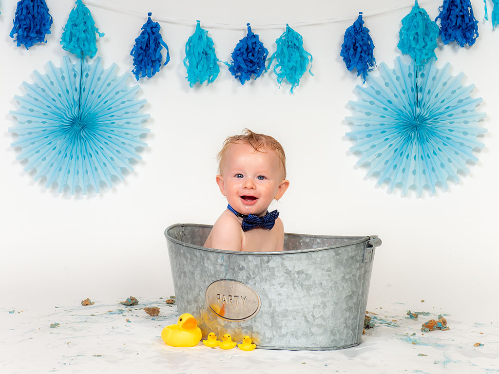 cake smash photography of little boy in bubble bath with rubber ducks taken by qualified family photographer in Braintree, Essex