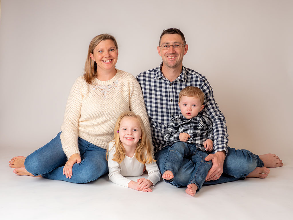 happy family sitting on floor in photography studio taken by qualified family phtographer trebor photography in Braintree, Essex