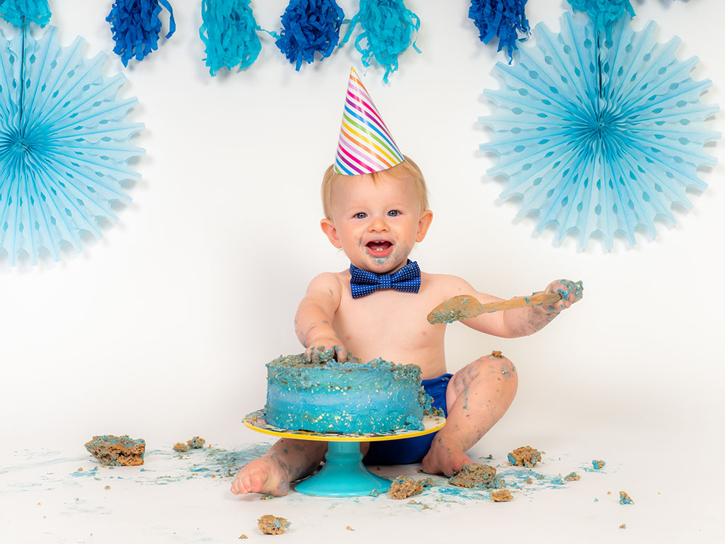 baby boy wearing party pat smashing blue cake with wooden spoon taken by cake smash photographer in Braintree