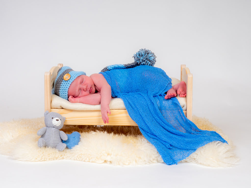 newborn baby asleep on bed taken by newborn photographer in Braintree
