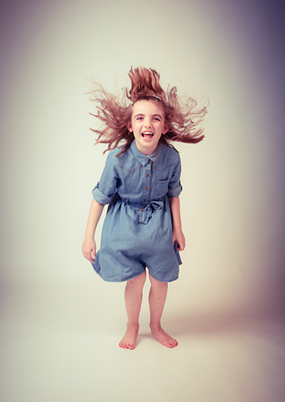 Young girl in demin dress jumping in the air with hair flowing around face