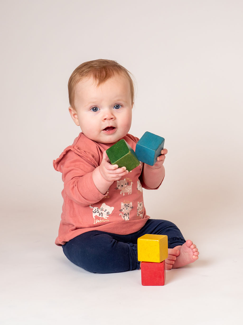 9 month old baby girl playing with wooden colourful bricks sitting on the floor taken by qualified baby photographer in Braintree, Essex