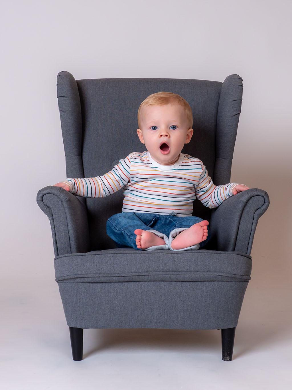 baby boy yawning while chiling in the armchair taken by qualified baby photographer in Braintree, Essex
