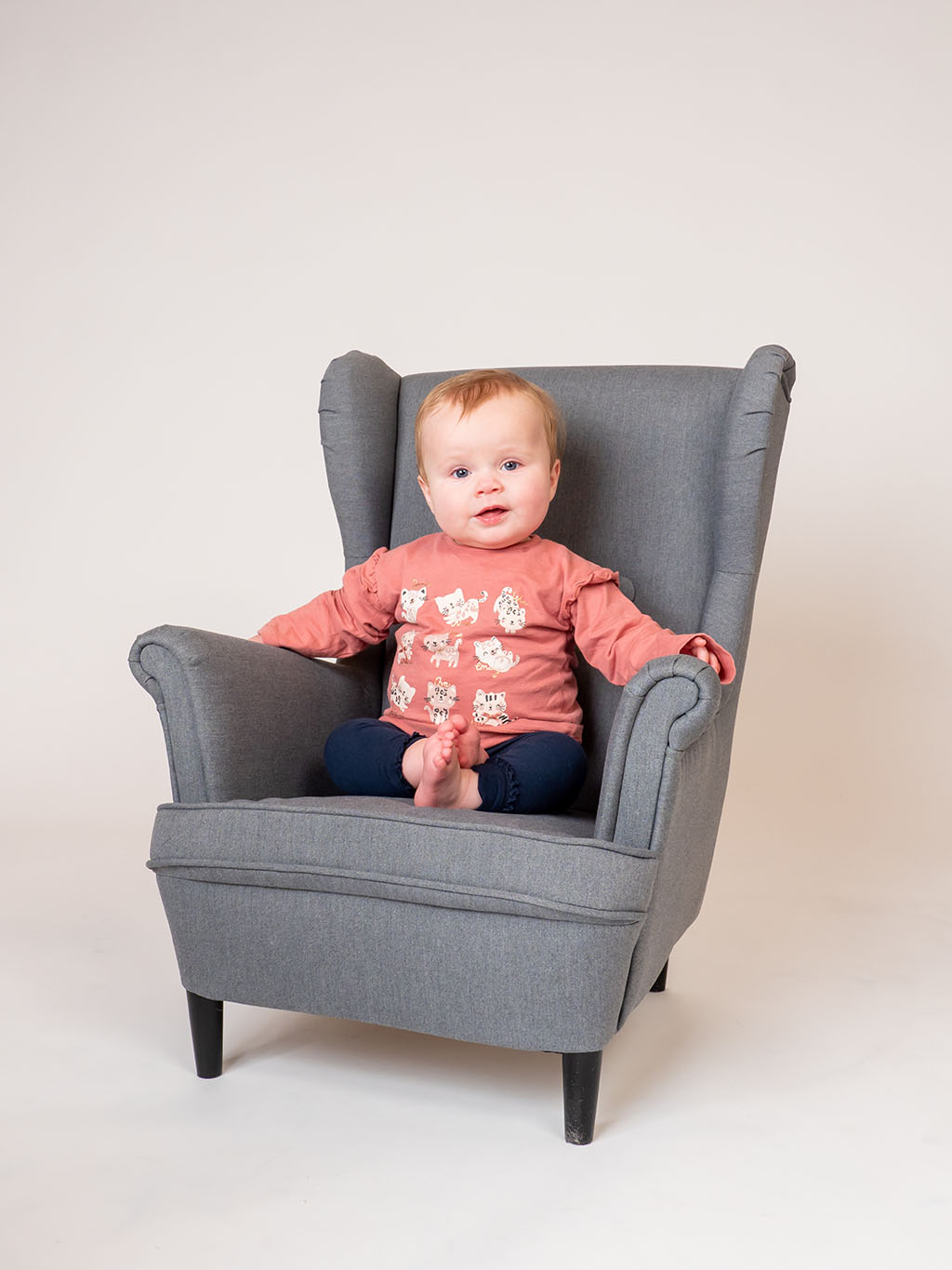 baby girl relaxing in armchair wearing pink top taken by qualified baby photographer in Braintree, Essex