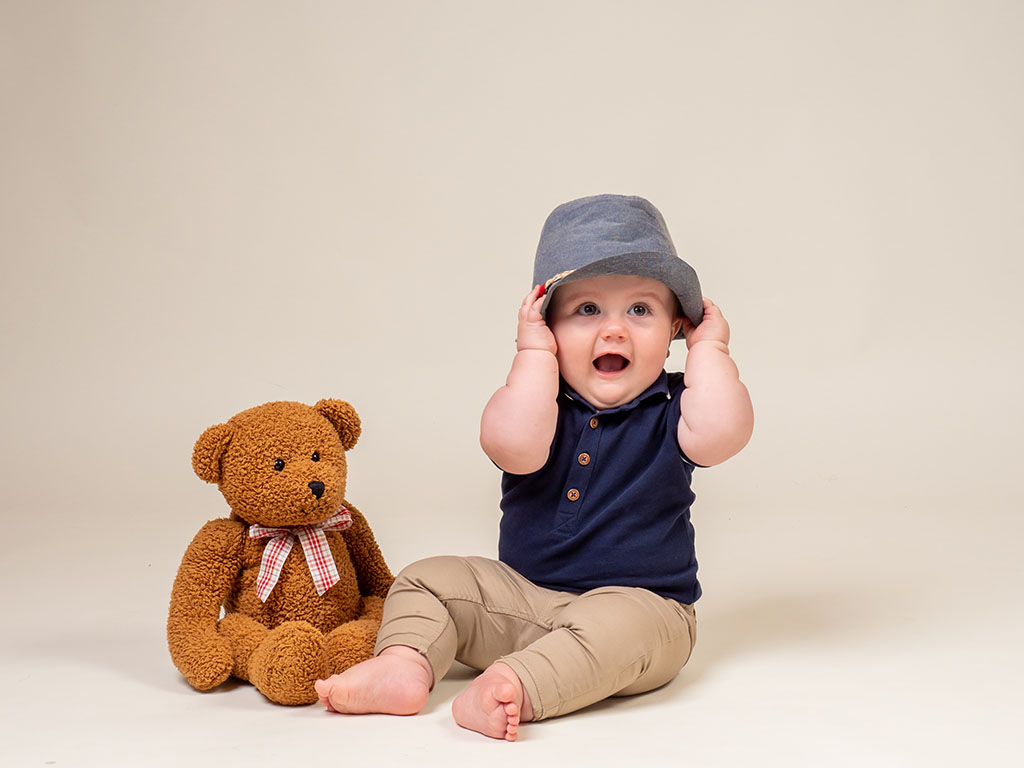 little boy sitting next to teddy bear holding hat on head against a cream background