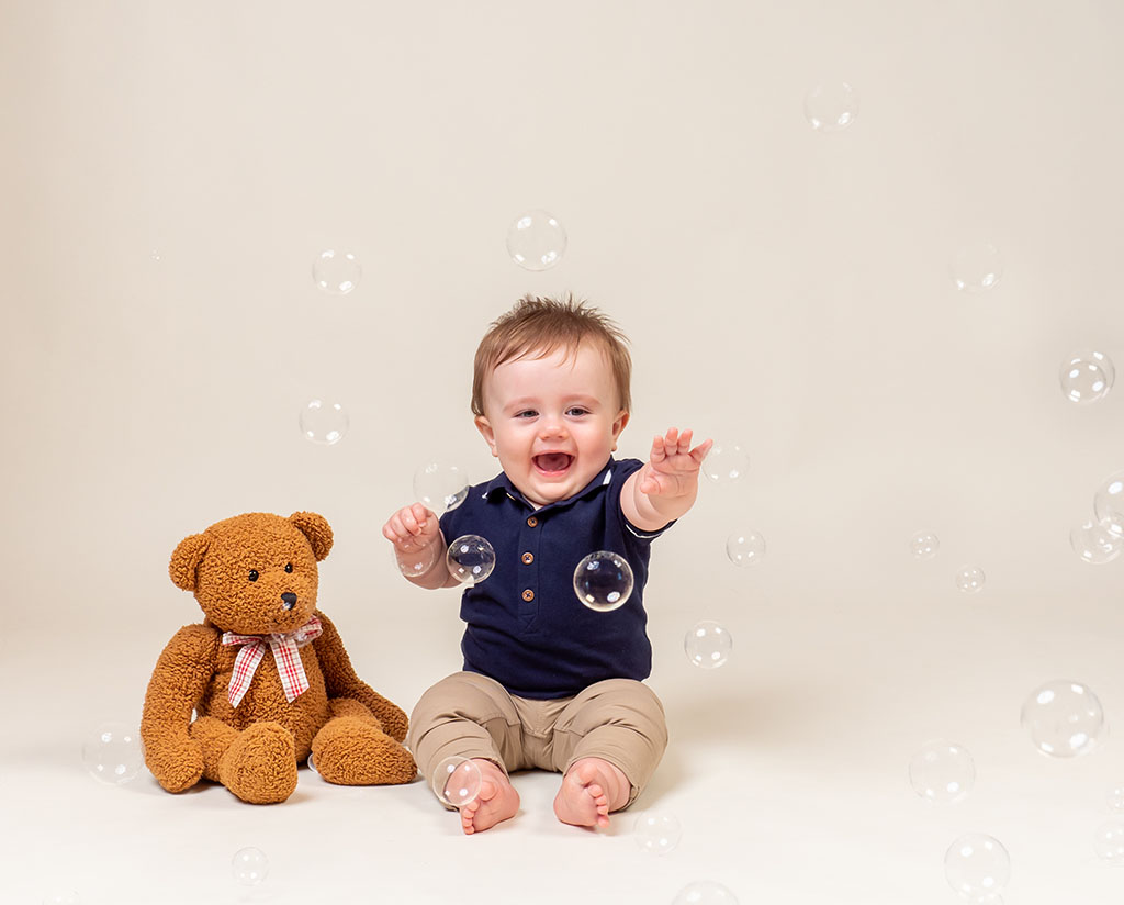 little boy sitting next to teddy bear playing with bubbles against a cream background