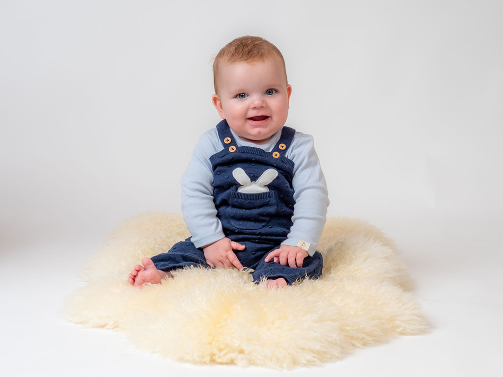 11 month old sitting up on sheepskin rug smiling at you taken by qualified baby photographer in Braintree, Essex