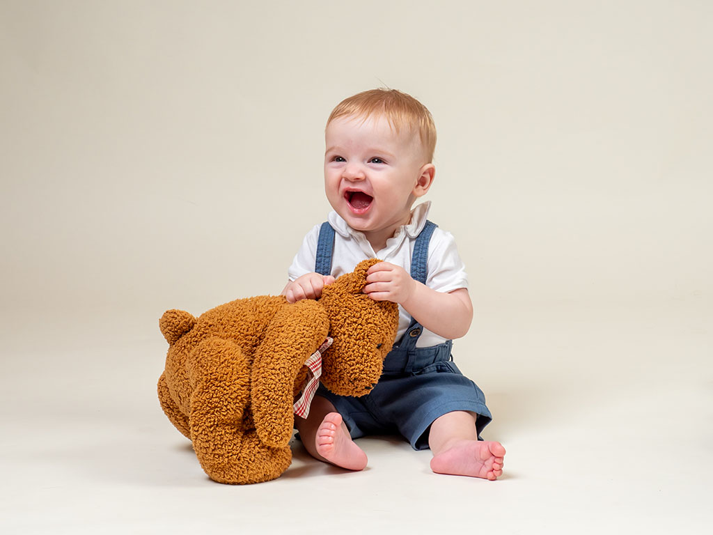 8 month old baby sitting up little sitters with his teddy bear taken by qualified baby photographer in Braintree, Essex