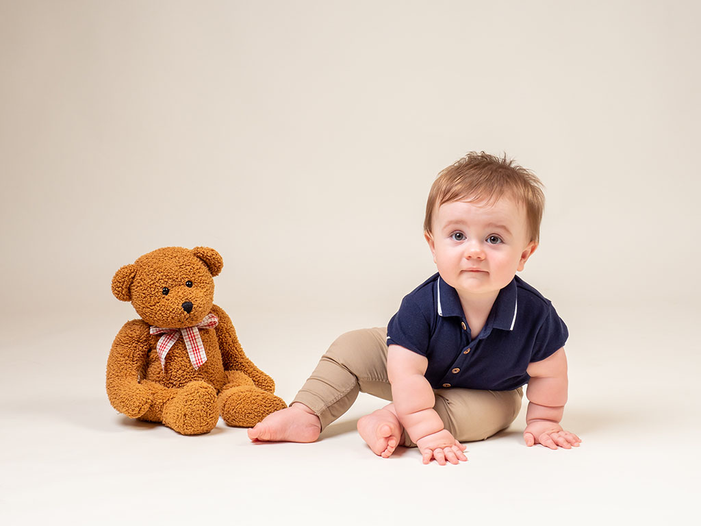 baby boy crawling with his teddy bear taken by qualified baby photographer in Braintree, Essex