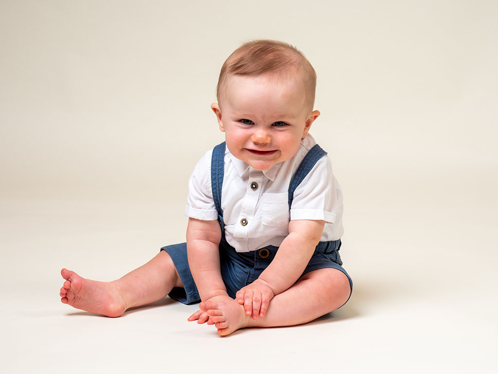 baby boy sitting up unaided with a smile taken by qualified baby photographer in Braintree, Essex