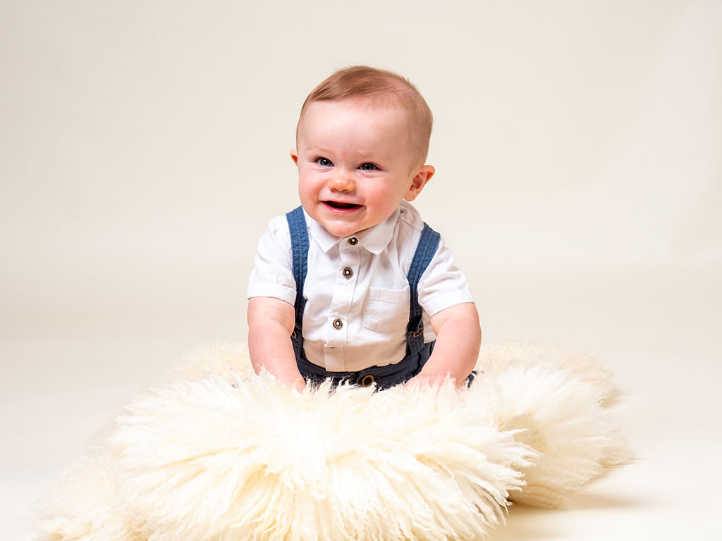 baby boy smiling and giggling playing wearing braces outfit taken by qualified baby photographer in Braintree, Essex