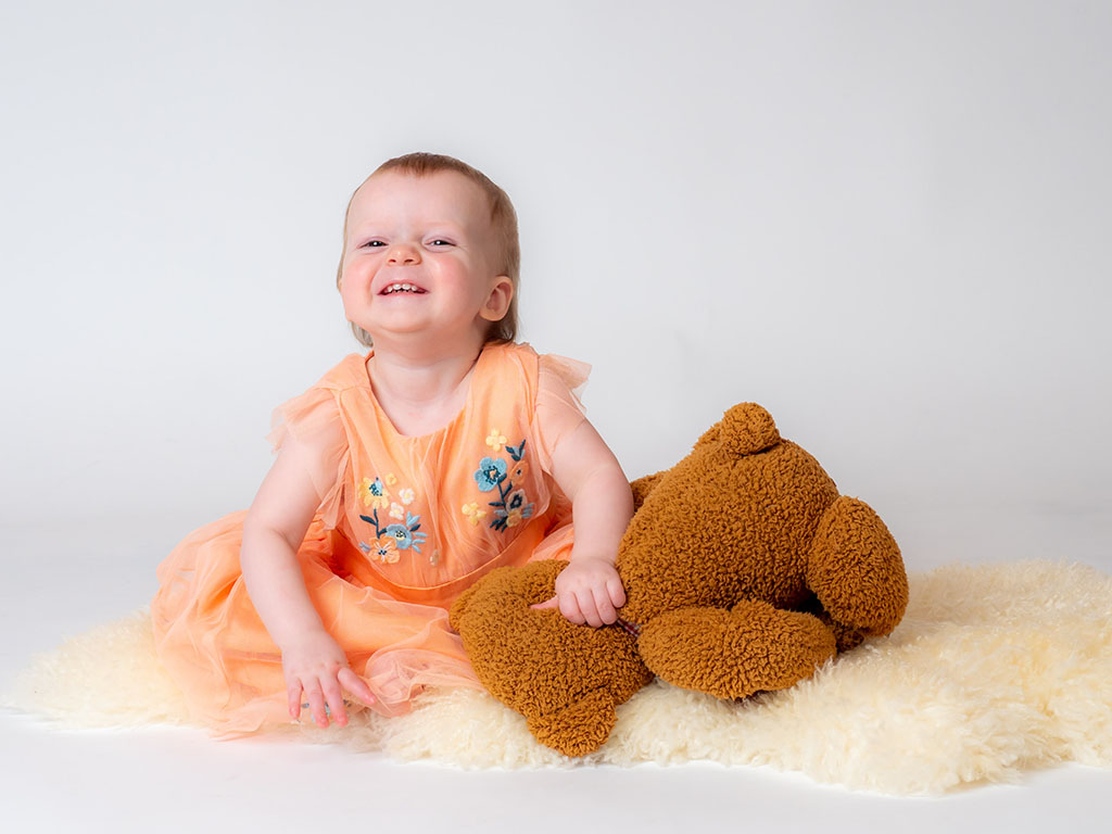 baby girl smiling and grinning with her teddy bear taken by qualified baby photographer in Braintree, Essex
