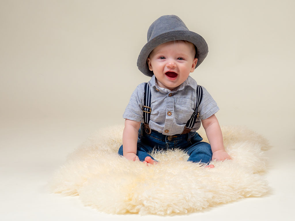 cute baby sitting up with trendy hat and braces outfit taken by qualified baby photographer in Braintree, Essex