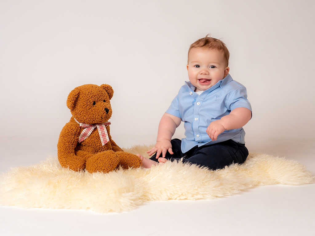 small baby smiling with his teddy bear wearing a smart shirt taken by qualified baby photographer in Braintree, Essex