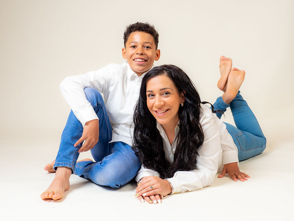 Mum lying on floor of photography studio with son sitting next to her both smiling